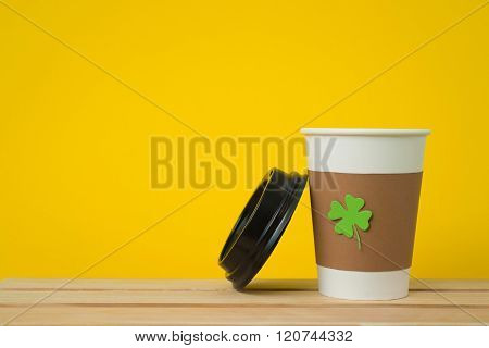 take away cup with cut and pasted green shamrock symbol and cover on wood board  on orange background