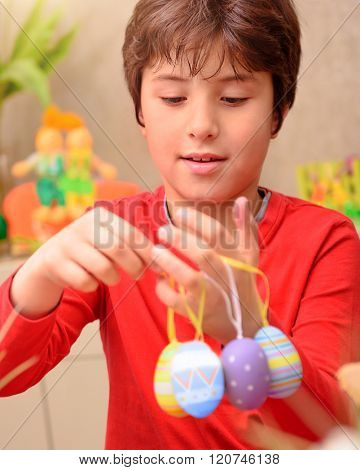 Portrait of cute boy play with beautiful colorful decorated eggs at home, with pleasure anticipate happy Easter holiday