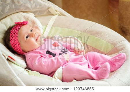 Little beautiful girl lies in a cradle