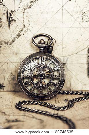 Vintage clock on antique map. Retro still life