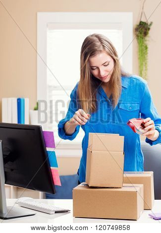 Young Woman Packing Boxes In Her Home Office