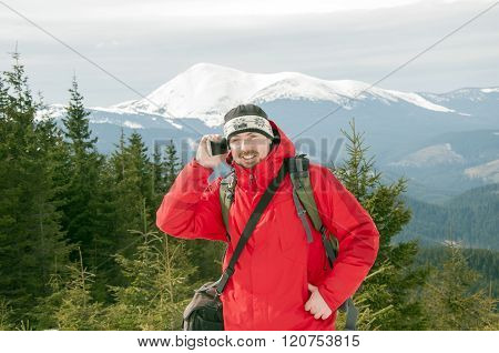 Hiker Talking On The Smartphone In The Winter Mountains