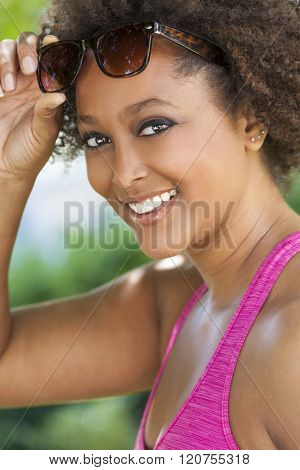 Beautiful young mixed race black African American woman with perfect teeth smiling and wearing lifting her sunglasses outside in summer sunshine