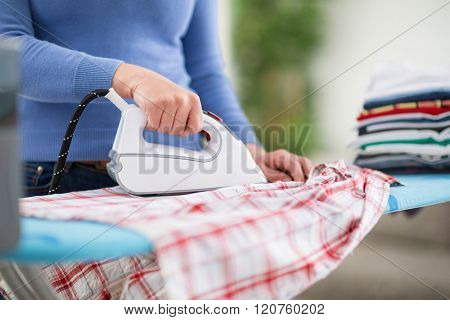 Woman from ironing services professionally iron clothes