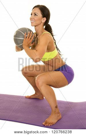 a woman doing a squat with a weighted medicine ball with a tattoo on her ankle.