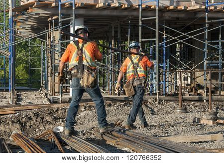 Workers Transporting Metal Rods