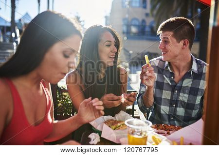 happy couple sharing french fry at outdoor restaurant
