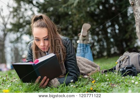 Closeup of a beautiful young woman reading book