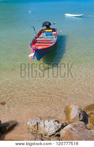 Colored wooden boat on the coast with transparent waters.