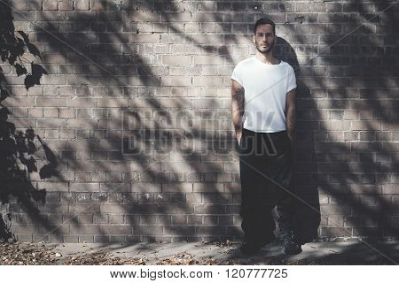 Bearded man with tattoo wearing blank white tshirt and black jeans. Bricks wall background. Horizont