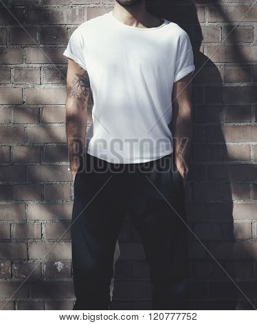 Man with tattoo wearing blank white tshirt and black jeans. Bricks wall background. Horizontal