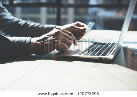 Man working with generic design notebook. Online payments plastic card, hands keyboard. Blurred back