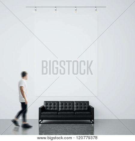 Photo of man in gallery. Waching empty canvas hanging on the brick wall and black generic design sof