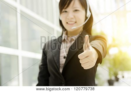 Portrait of a young Asian customer helpline with headset thumb up, at an office environment, natural golden sunlight at background.