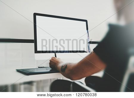 Man working at workspace with generic design computer on the table. Blank screen desktop. Horizontal
