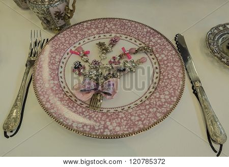 Pink plate with jewels and silver cutlery