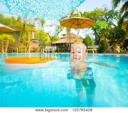 Cute caucasian boy enjoys of swimming pool