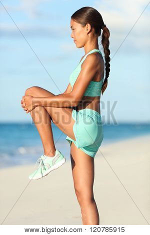 Fitness runner woman doing warm-up routine on beach before running, stretching leg muscles with standing single knee to chest stretch. Female athlete preparing legs for cardio workout in sportswear.