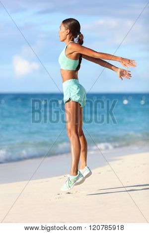 Fit woman training legs with hiit workout jumping squats exercises. Fitness training doing cardio exercise on summer ocean white sand beach doing explosive jumps and burpees to activate the glutes.