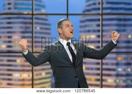 Adult joyful businessman near window.