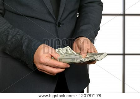 Adult office worker counting cash.