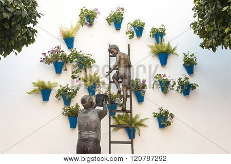 Granny And His Grandson Placing Flowerpots On The Wall, Cordoba, Spain