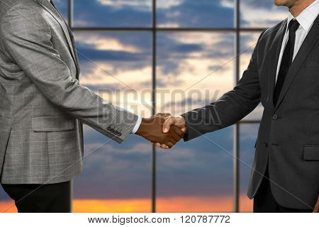 Politicians shake hands at sunset.