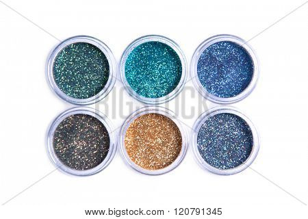 Bright cosmetic glitters in transparent jars, top view isolated on white background