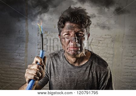 young man holding electrical cable smoking after domestic accident with dirty burnt face in funny sad expression in electricity DIY repairs danger concept in black smoke background