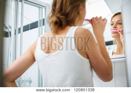 Pretty female brushing her teeth in front of mirror in the morning