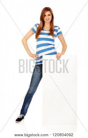 Happy teenage woman with blank billboard