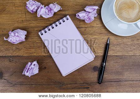 Notebook with pen aside coffee crumpled paper on wooden table
