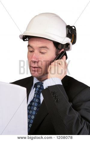 Architect Reading Plans And Using Mobile Phone