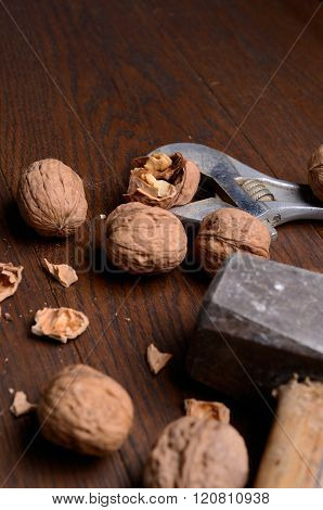 Cracking nuts with heavy tools on a wooden table