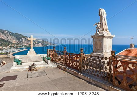 Statue and tomb with cross at old cemetery with view on Mediterranean sea in Menton, France.