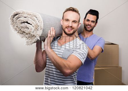 Gay couple carrying rolled up carpet at new home