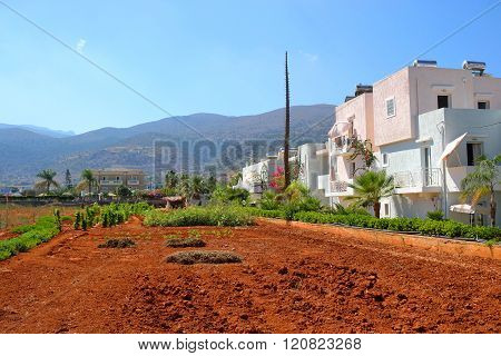 View of red arable land Malia town and mountain on Crete island Greece.