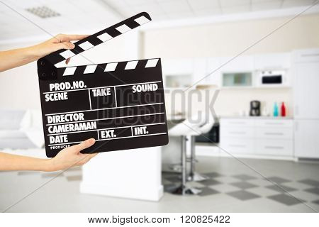Operator holding clapperboard during the production of film indoors