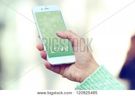 Female hand holding a mobile phone with romantic screensaver, outdoors