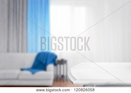 Empty wooden table on blurred room interior background