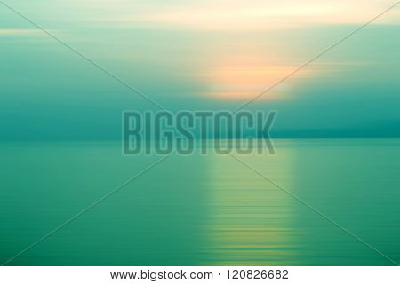 Abstract background motion blurred of refraction in water with sunset on the sea at twilight times - Emerald Tone