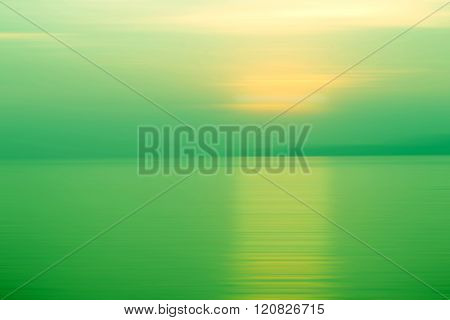 Abstract background motion blurred of refraction in water with sunset on the sea at twilight times - Green Tone
