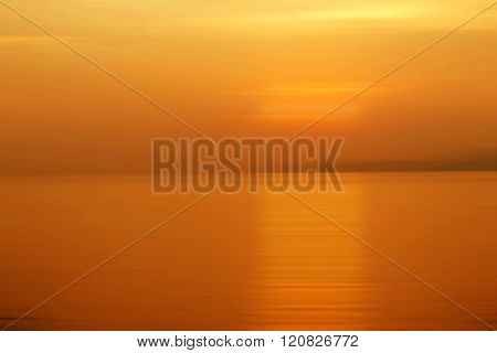 Abstract background motion blurred of refraction in water with sunset on the sea at twilight times - Orange Tone