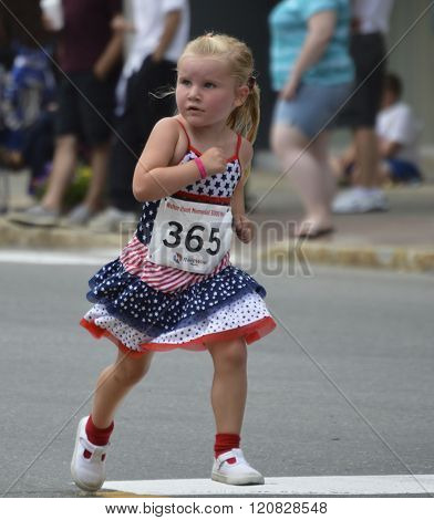 Bangor, Maine/USA-July 4: A cute blond girl dressed in a red, white, and blue dress, runs in the 2015 4th of July Parade race on Main St. in downtown Bangor, Maine.