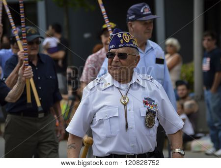 Bangor, Maine/USA-July 4: Old war veterans march proudly in the 2015 4th of July Parade in downtown Bangor, Maine. They salute by raising their canes.
