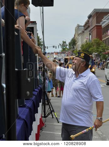 Bangor, Maine/USA-July 4: A Veteran marching the in the 4th of July Parade in downtown Bangor, Maine in 2015, takes a moment to shake the hand of a boy on the sidelines.