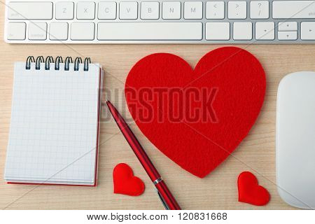 Computer peripherals with red hearts, pen and notebook on light wooden table
