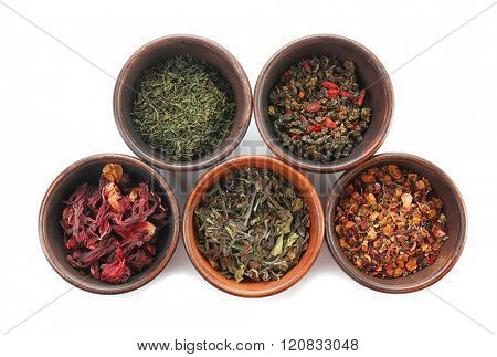 Variety of dry tea in pots isolated on white, top view