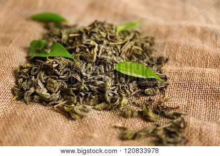 Granulated tea with green leaves on sackcloth background