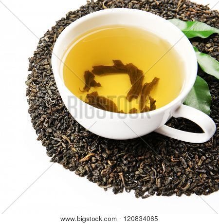 Cup with brewed dry tea and green leaves, isolated on white